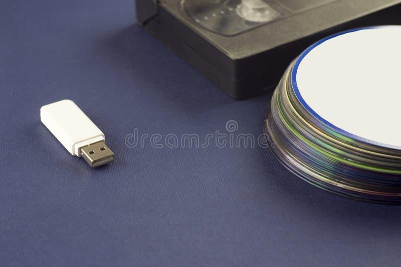 在蓝色背景录象带和雷射唱片usb的白色一刹那驱动 库存照片