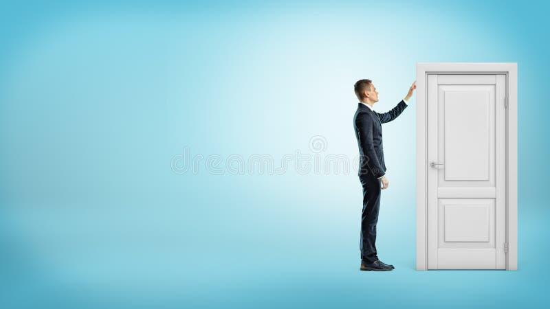 在蓝色背景的一个商人接触与绝密里面的一个白色门框 免版税库存图片