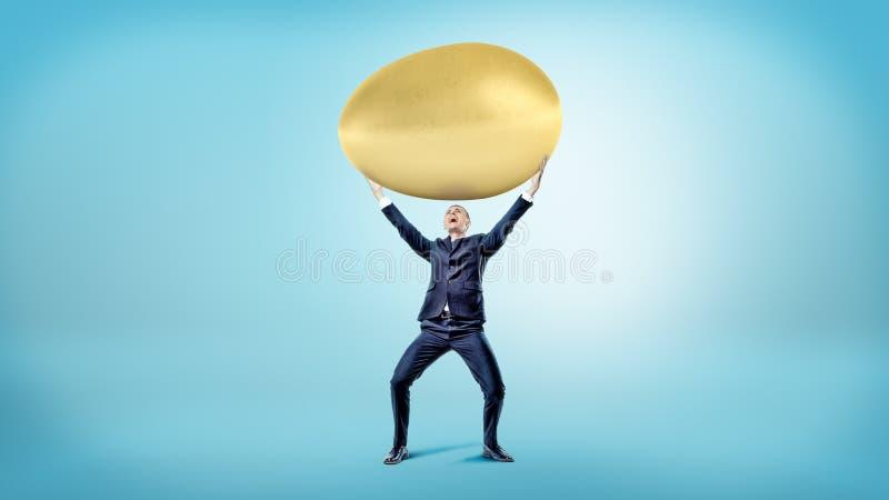 在蓝色背景的一个愉快的商人拿着在他的头的一个巨大的金黄鸡蛋 免版税图库摄影