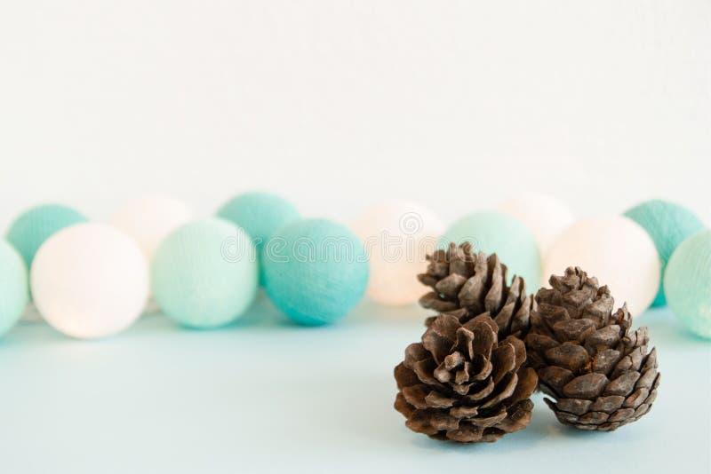 在蓝色背景的三个锥体与蓝色和白光由毛线制成穿线 圣诞节装饰生态学木 库存照片