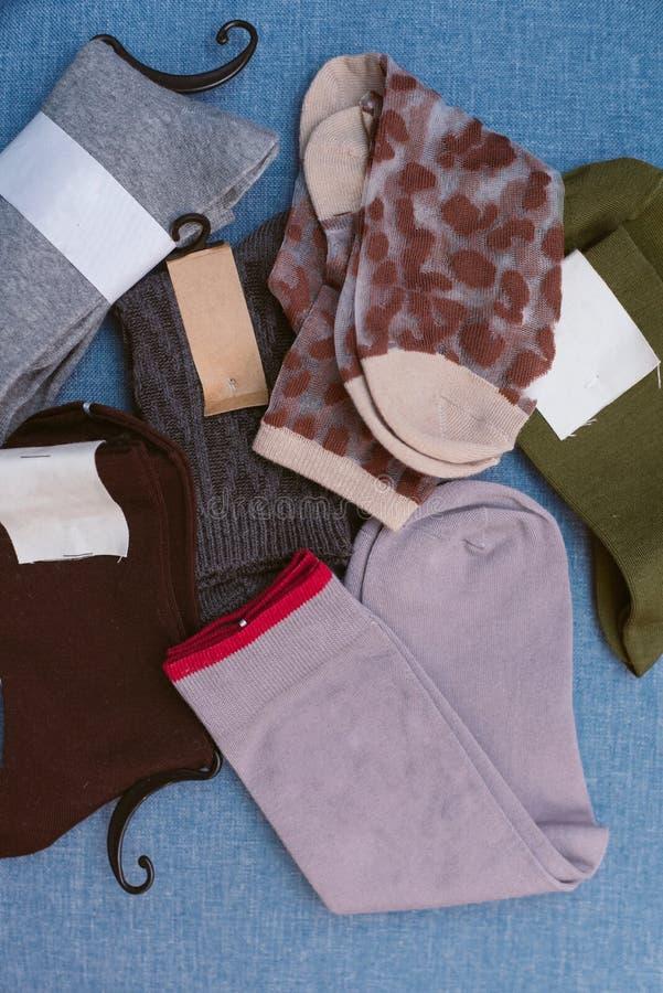 在蓝色背景的不同的色的时髦的袜子 免版税库存照片