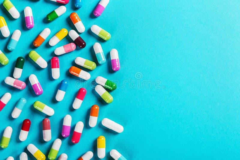 在蓝色背景的不同的颜色药片 图库摄影