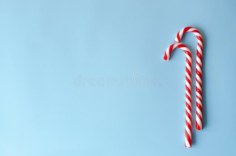 在蓝色背景的两个藤茎糖果 免版税库存图片