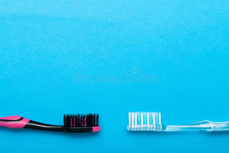 在蓝色背景的五颜六色的塑料牙刷 文本的空的拷贝空间 免版税图库摄影