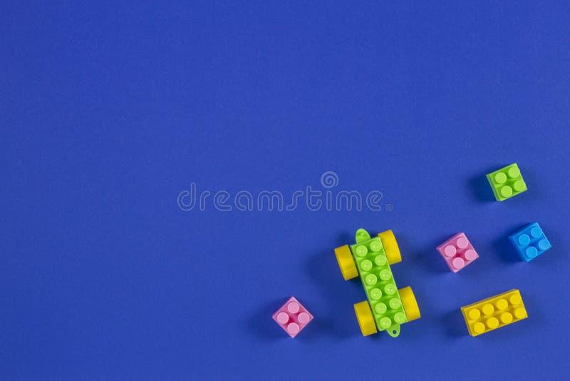 在蓝色背景的五颜六色的塑料玩具汽车积木 免版税图库摄影