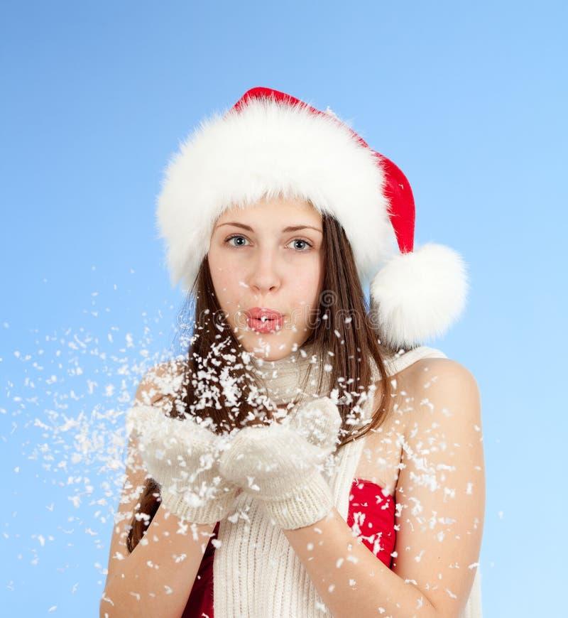 在蓝色背景的圣诞节女孩吹的雪 库存图片