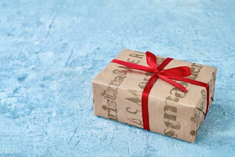 在蓝色背景的圣诞节纸包裹的礼物盒 复制温泉 库存图片