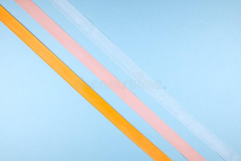 在蓝色背景的多彩多姿的丝带 简单派概念 免版税库存照片