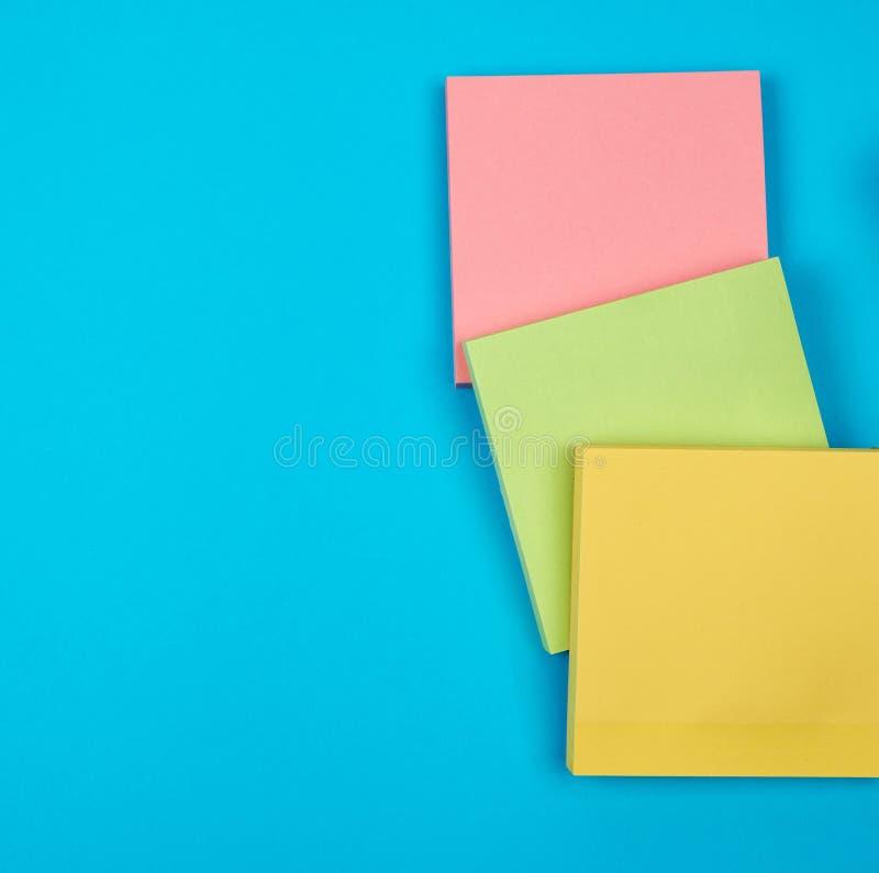 在蓝色背景的多彩多姿的空的纸正方形贴纸 库存照片
