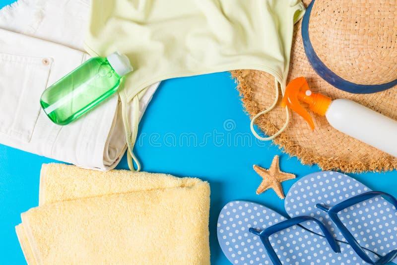 在蓝色背景的妇女夏天成套装备顶视图 时尚假期概念 免版税库存照片