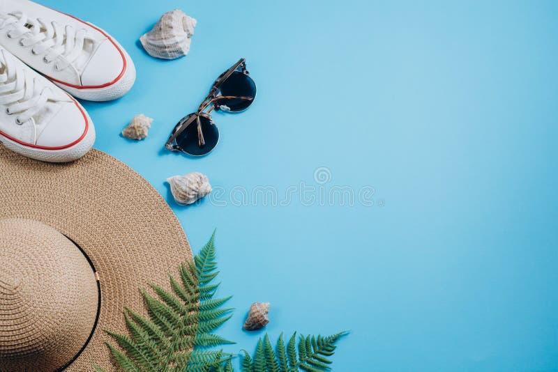 在蓝色背景的平的被放置的旅客辅助部件与热带蕨叶子分支、鞋类、帽子和贝壳 免版税库存照片