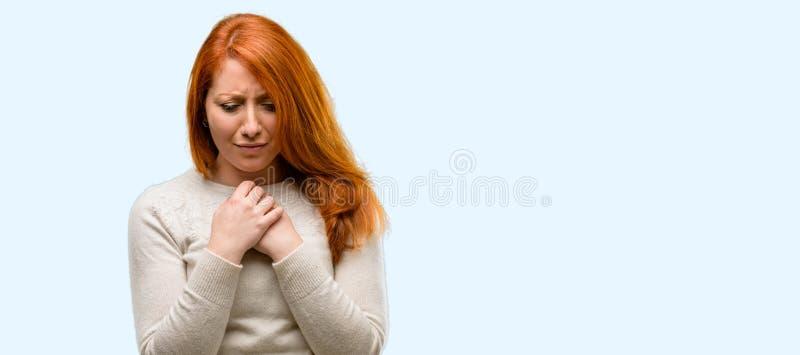 在蓝色背景的年轻美丽的红头发人妇女 图库摄影