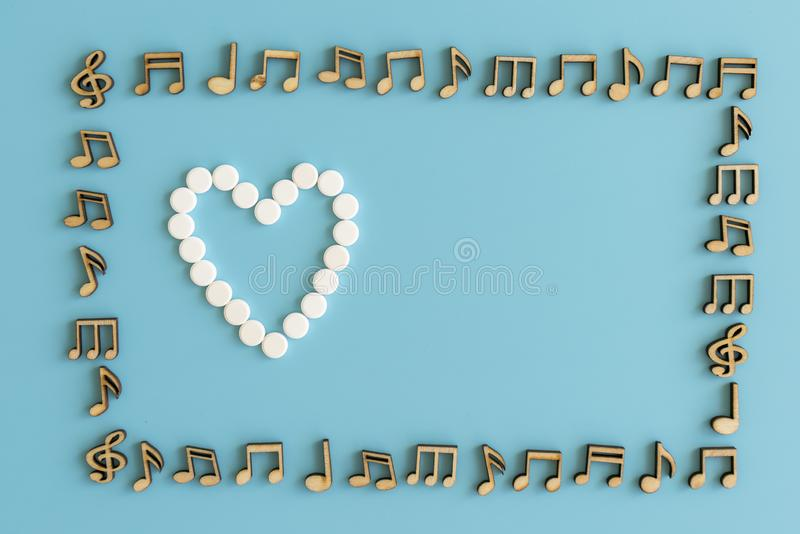 在蓝色背景的心脏概念 白色药片的心脏在蓝色背景的 笔记框架 免版税库存照片
