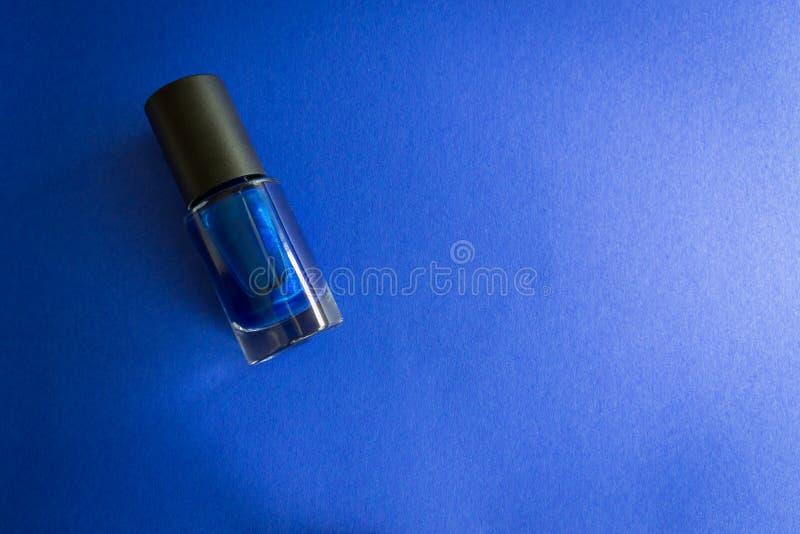 在蓝色背景的指甲油瓶 免版税库存照片