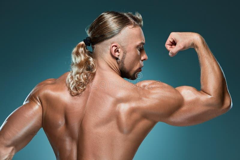 在蓝色背景的有吸引力的男性身体建造者 库存图片