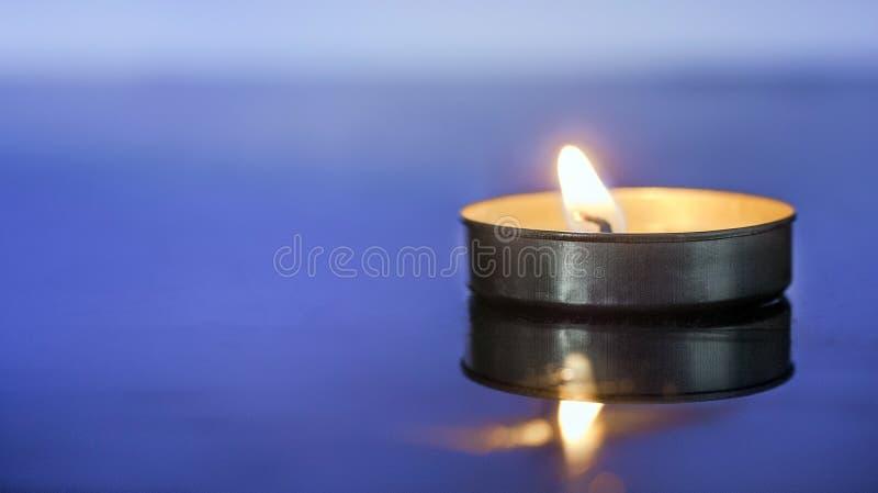 在蓝色背景的有气味的蜡烛光 免版税库存图片