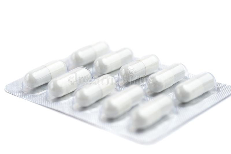 在蓝色背景的水泡包装的医学白色药片 库存照片