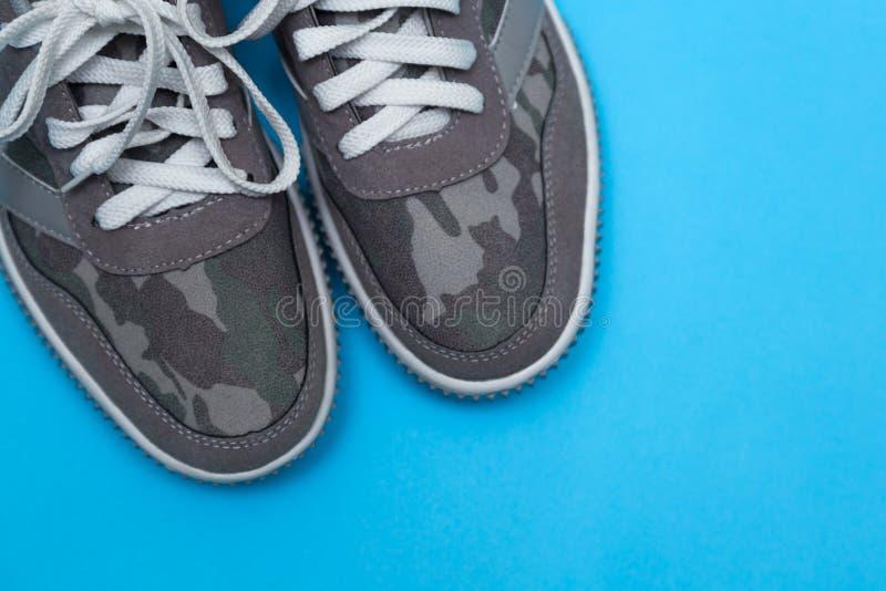 在蓝色背景的灰色运动鞋 免版税图库摄影
