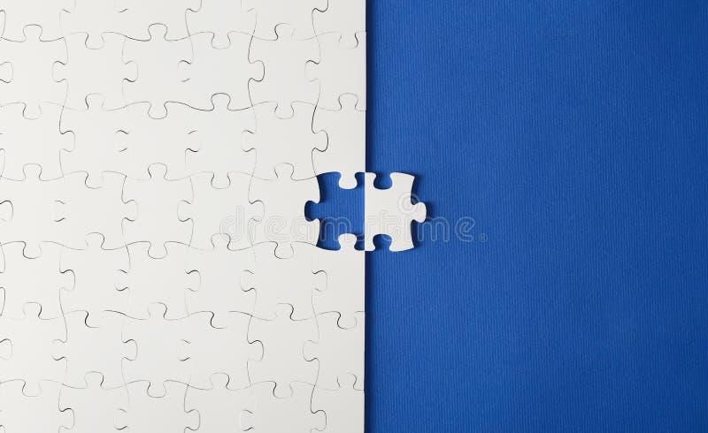 在蓝色背景的白色难题与一个错过的片断 免版税库存照片