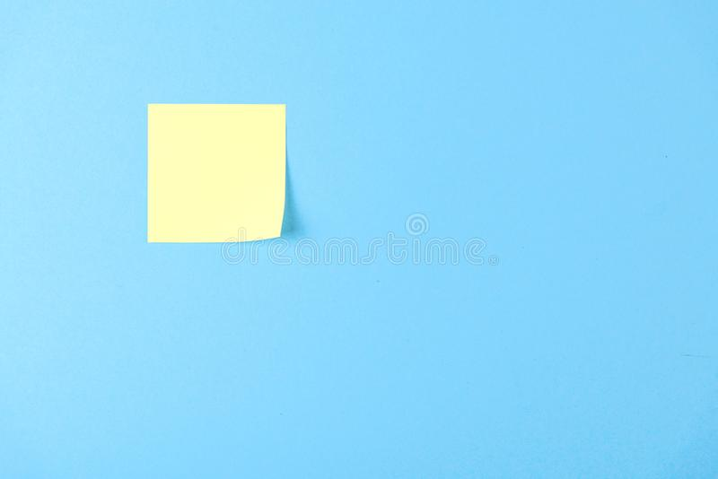 在蓝色背景的空白的黄色贴纸,企业工作概念 在蓝色墙壁上的黄色纪念贴纸 r 库存照片