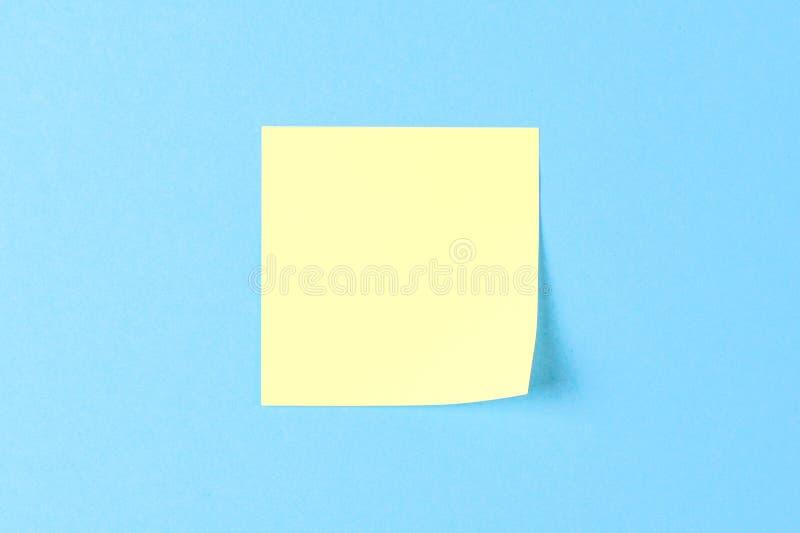 在蓝色背景的空白的黄色贴纸,企业工作概念 在蓝色墙壁上的黄色纪念贴纸 r 免版税库存图片