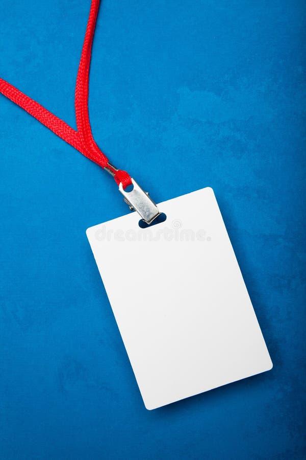 在蓝色背景的空的白色空白的徽章与红色脖子 库存照片