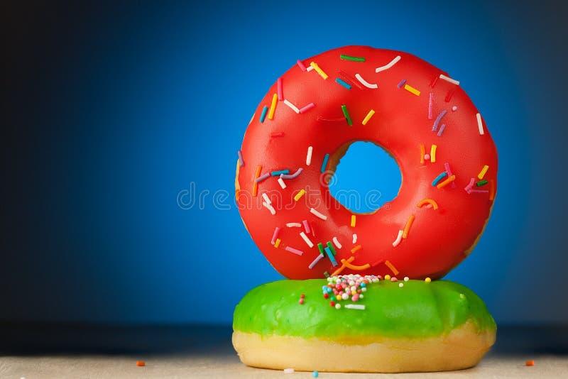 在蓝色背景的红色和绿色油炸圈饼 免版税库存照片