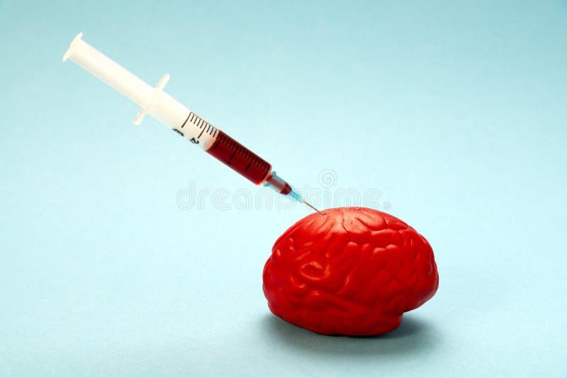 在蓝色背景的红色脑子与一个nootropic注射器 射入到脑子里 库存图片