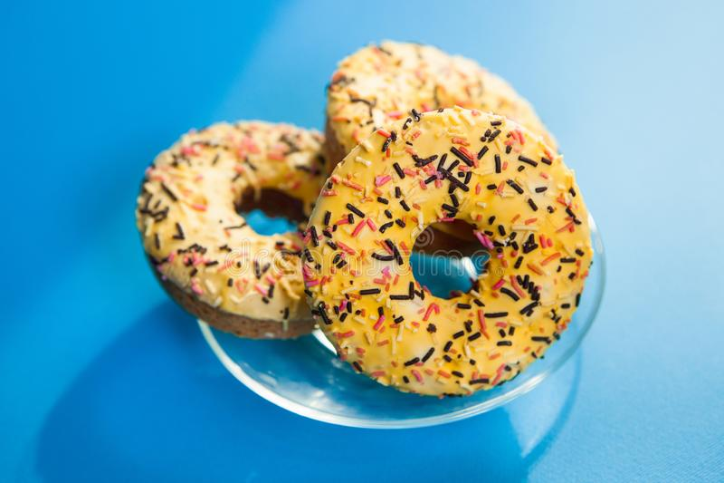 在蓝色背景的美丽的黄色油炸圈饼饼干与阳光,不健康的食物 免版税库存照片