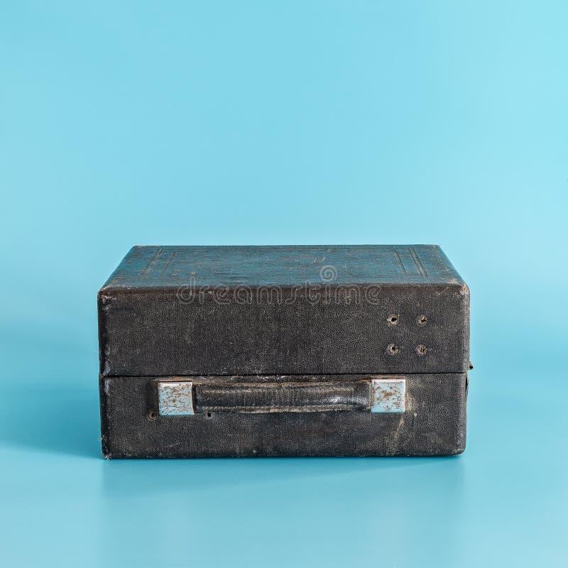 在蓝色背景的老黑破旧的闭合的手提箱 r 免版税库存图片