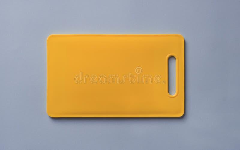 在蓝色背景的色的黄色塑料切板 免版税库存照片