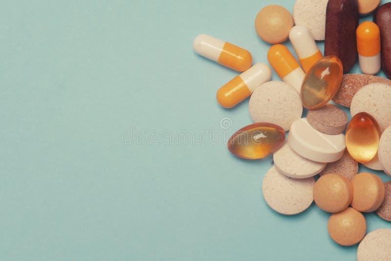 在蓝色背景的药片 被分类的配药医学药片、片剂和胶囊,健康宏指令 各种各样的药片堆  免版税库存照片