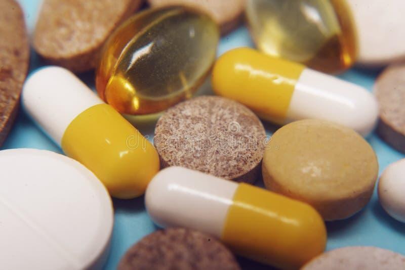 在蓝色背景的药片 被分类的配药医学药片、片剂和胶囊,健康宏指令 各种各样的药片堆  图库摄影