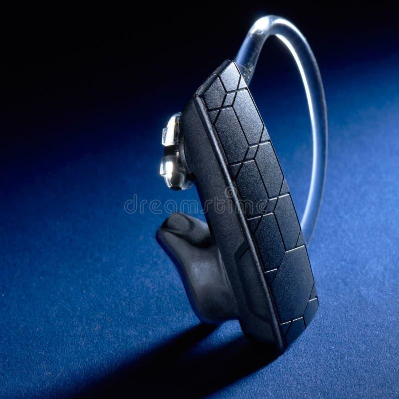 在蓝色背景的蓝牙耳机 免版税库存图片