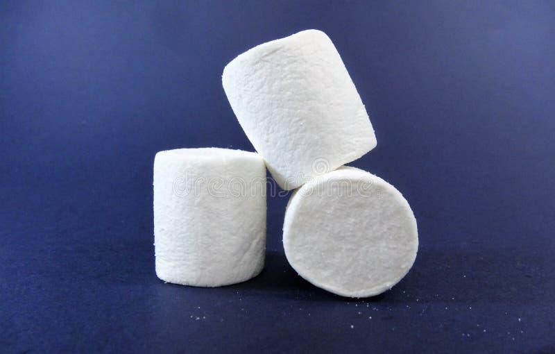 在蓝色背景的蛋白软糖白色糖果 免版税库存照片