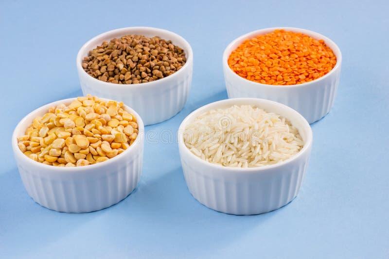 在蓝色背景的被分类的不同的谷物 荞麦,扁豆,米,在板材的豌豆在上面,地方的拷贝 库存图片