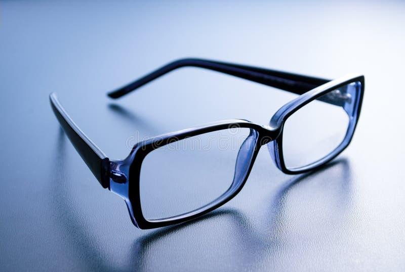 在蓝色背景的角质架眼镜 图库摄影