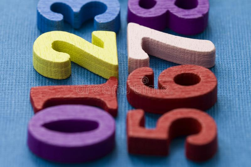 在蓝色背景的许多五颜六色的数字 容易的mathemanics概念 图库摄影