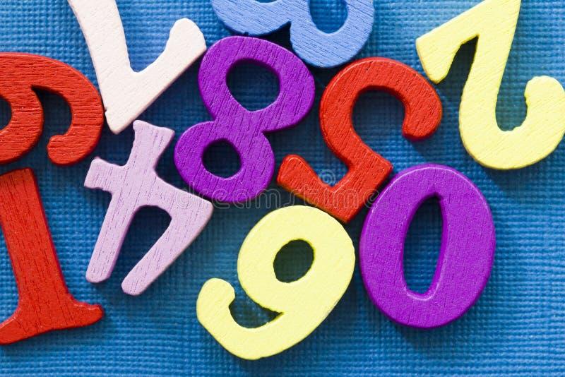 在蓝色背景的许多五颜六色的数字 容易的mathemanics概念 免版税图库摄影
