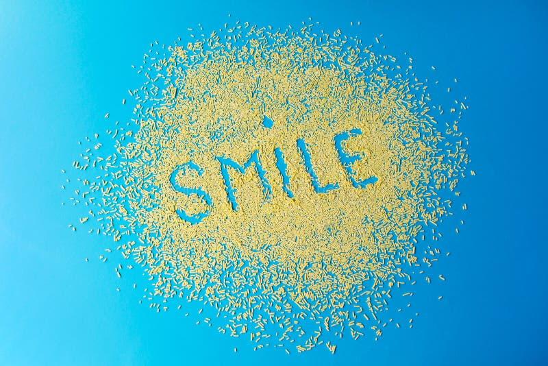 在蓝色背景的词微笑 糖果店洒 在蓝色的黄色糖五谷 图象纵向股票妇女年轻人 免版税库存照片