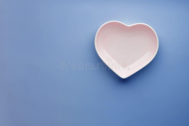 在蓝色背景的陶瓷光滑的心形的板材 时髦的浪漫碗筷 茶碟为情人节或 库存图片