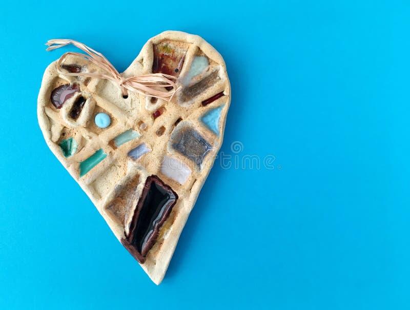 在蓝色背景的陶瓷心脏 艺术手工制造对象  免版税库存照片