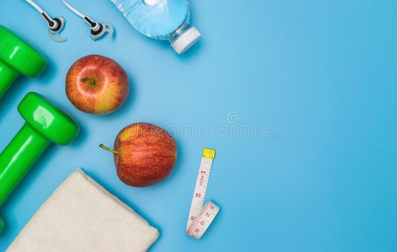 在蓝色背景的顶视图健康对象与哑铃、水和耳机体育或锻炼概念的 库存图片