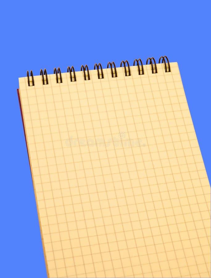 在蓝色背景的黄色笔记本 免版税库存照片