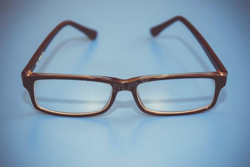 在蓝色背景的黑眼睛玻璃 时髦的设置 库存图片