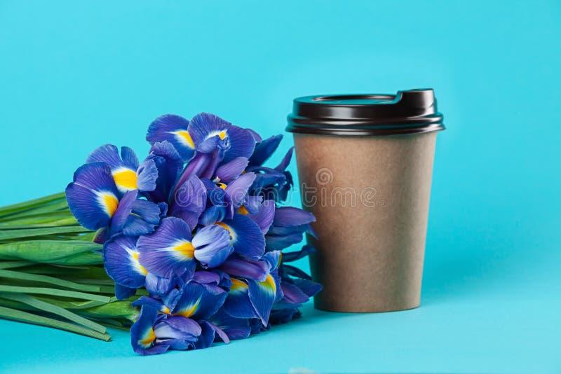 在蓝色背景隔绝的外带的纸咖啡杯大模型 库存图片