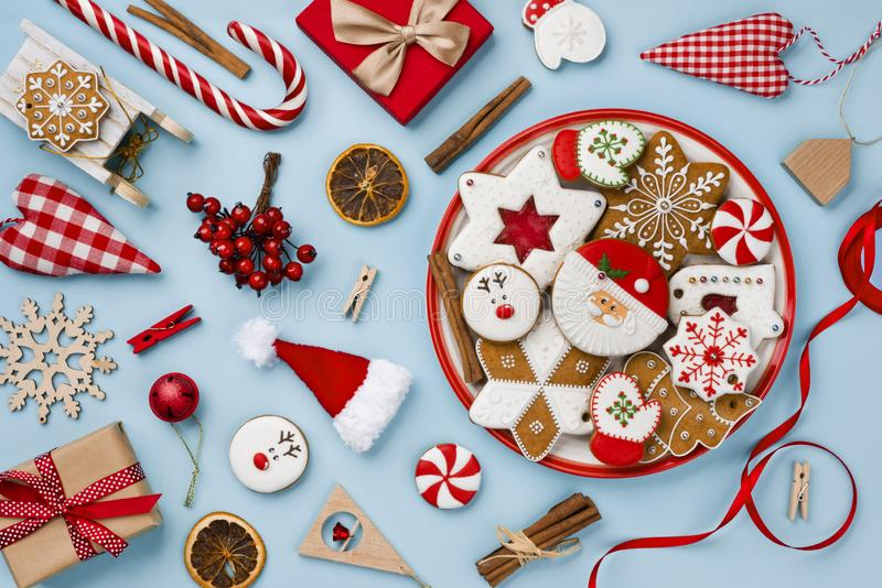 在蓝色背景隔绝的有吸引力的圣诞节姜饼和装饰玩具 图库摄影