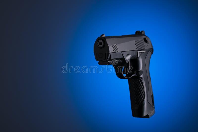 在蓝色背景隔绝的黑手枪 免版税库存图片