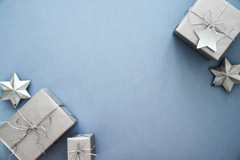 在蓝色背景顶视图的圣诞节银色手工制造礼物盒 圣诞快乐贺卡,框架 冬天xmas假日题材 免版税图库摄影