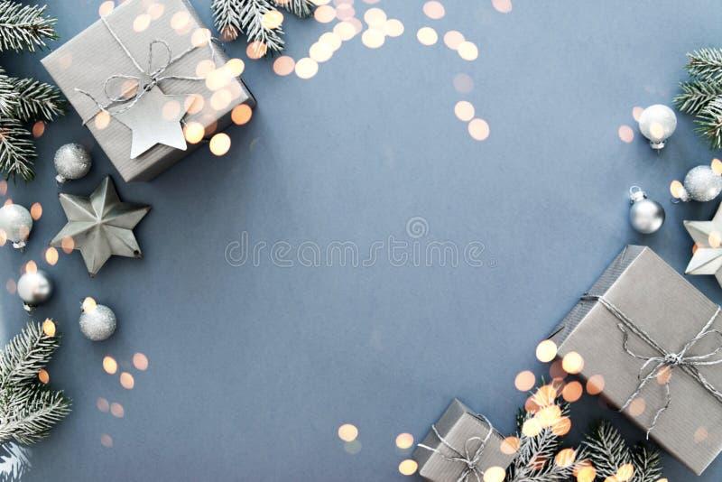 在蓝色背景顶视图的圣诞节银色手工制造礼物盒 圣诞快乐贺卡,框架 冬天xmas假日题材 库存图片